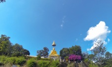 At the top of the biggest climb of the day, a monk stands underneath the Wat giving us a thumbs up!!!