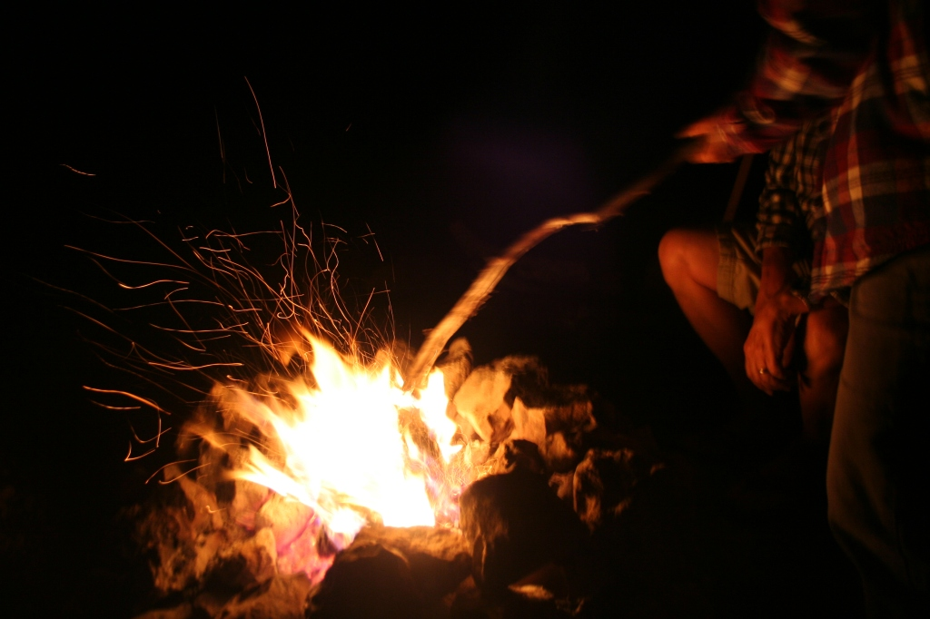 Campfire scene at night with sparks flying.
