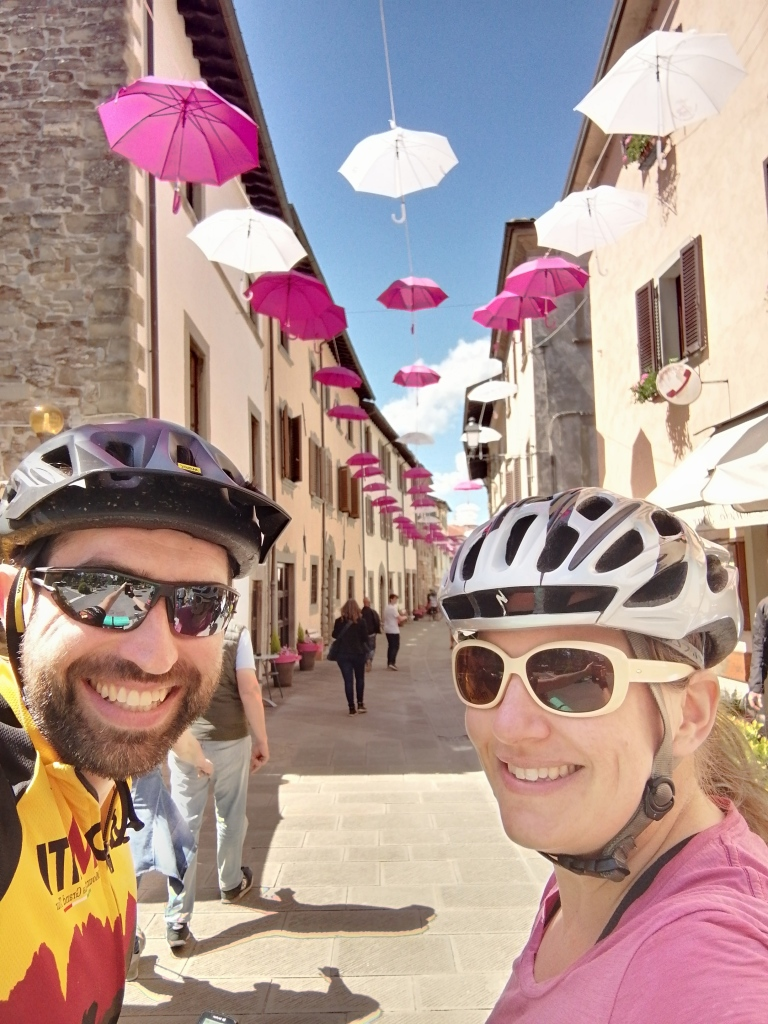 Two grinning bike tourists standing in front of Bagno di Romagna, still decorated with bright pink umbrellas in the sky for the Giro d'Italia.