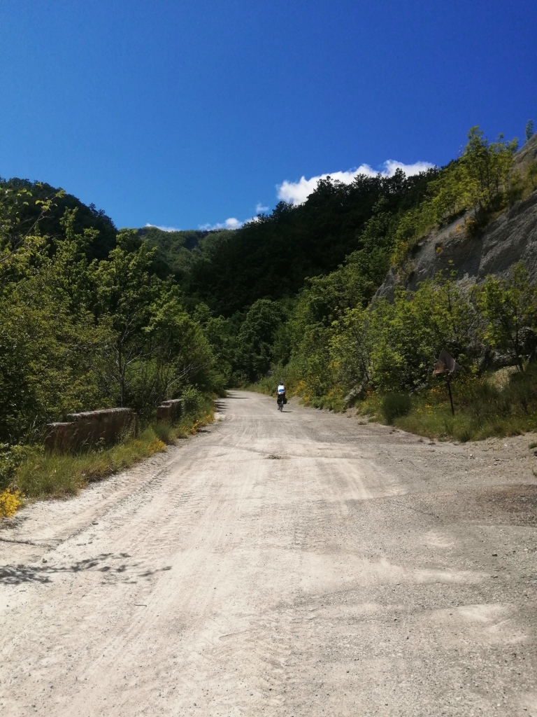 Two bike tourists on the closed E-45 highway outside of Bagno di Romagna. Nothing but sky and trees.