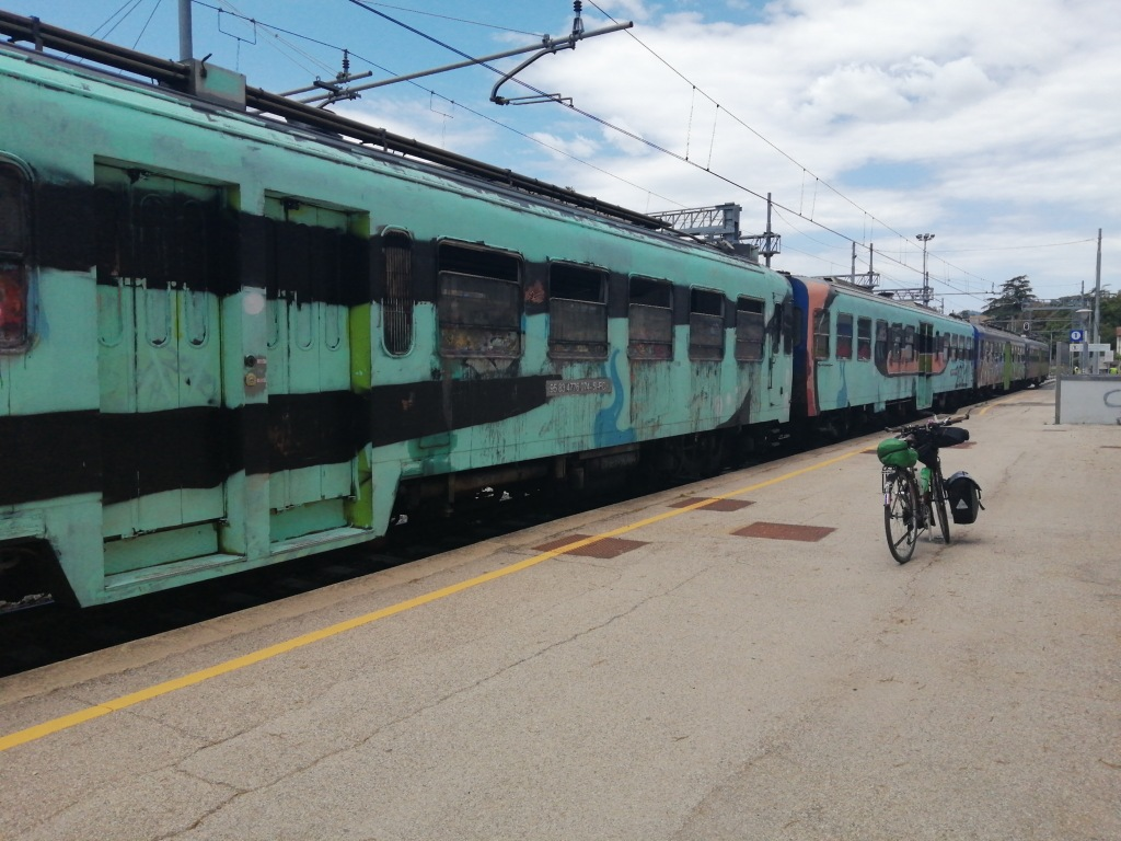 A graffiti-covered train and a bike at a deserted train station in Umbertide, Umbria.