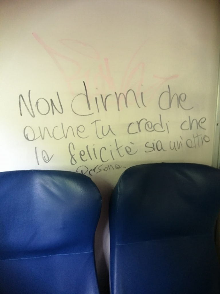 """A message on the train in Italian that means, """"Don't tell me that you, too believe that happiness is only found in another person."""""""